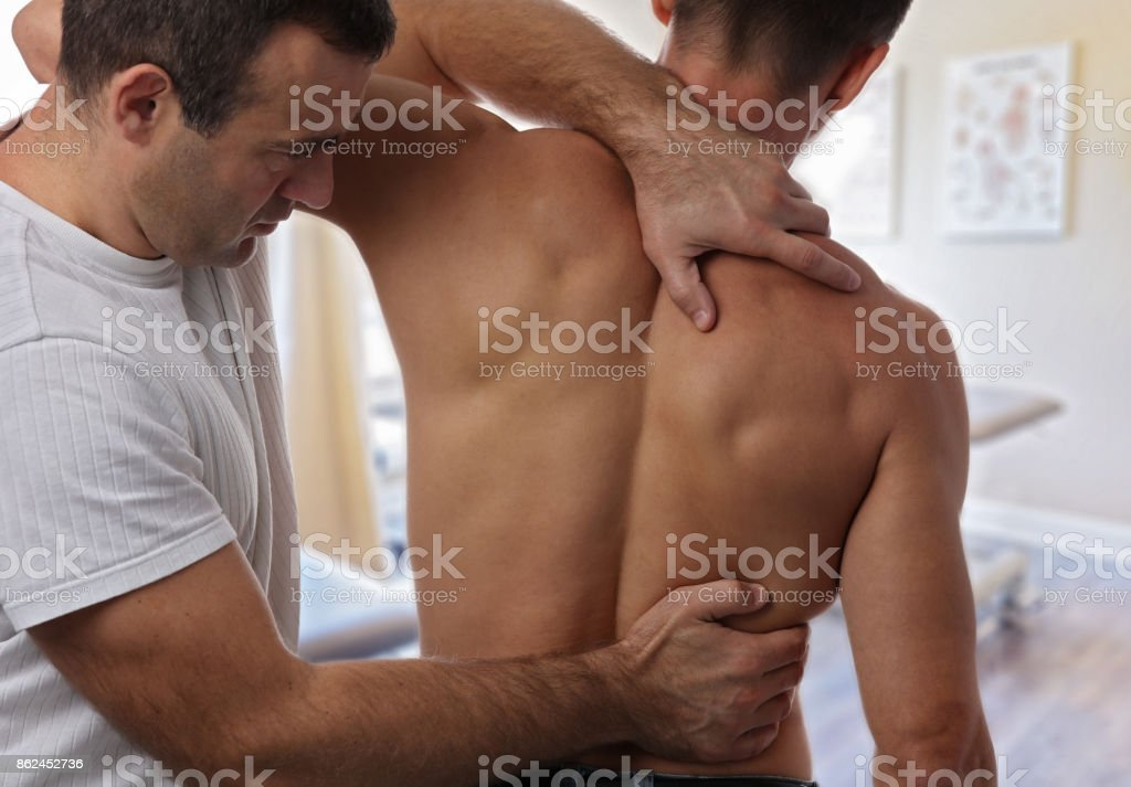 Chiropractic back adjustment. Muscular Man suffering from back and neck pain. stock photo