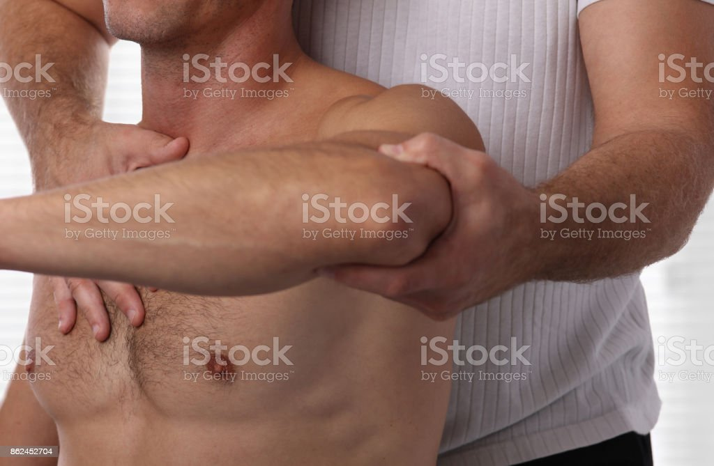 Chiropractic back adjustment. Muscular Man suffering from back pain. stock photo