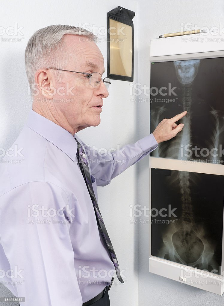 Chiropractic Doctor Points to Spinal Image on X-ray royalty-free stock photo
