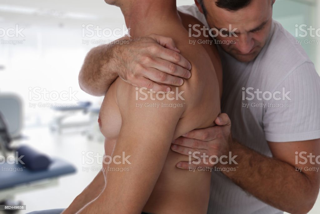 Chiropractic, osteopathy, manual therapy, acupressure. Therapist doing healing treatment on man's back. Alternative medicine, pain relief concept stock photo