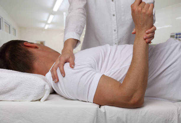 Chiropractic, osteopathy, manual therapy. Therapist doing healing treatment on man's back. Alternative medicine, pain relief concept. Physiotherapy, sport injury rehabilitation stock photo