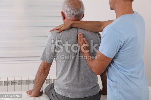 885281276istockphoto Chiropractic / Osteopathy treatment, Back pain relief. Physiotherapy for senior male patient, sport injury recovery , Kinesiology 1177308707