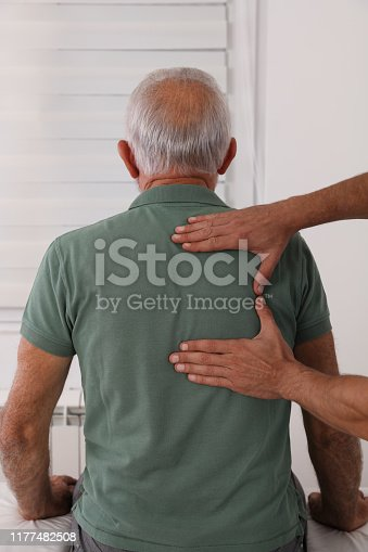 885281276istockphoto Chiropractic / Osteopathy treatment, Back pain relief. Physiotherapy for senior male patient, sport injury recovery , Kinesiology 1177482508