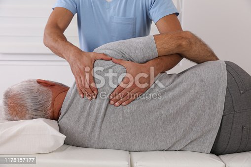885281276istockphoto Chiropractic / Osteopathy treatment, Back pain relief. Physiotherapy for senior male patient, sport injury recovery , Kinesiology 1178157177