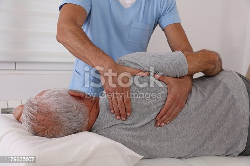885281276istockphoto Chiropractic / Osteopathy treatment, Back pain relief. Physiotherapy for senior male patient, Kinesiology 1179635807