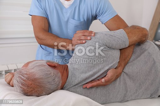 885281276istockphoto Chiropractic / Osteopathy treatment, Back pain relief. Physiotherapy for senior male patient, Kinesiology 1179635809