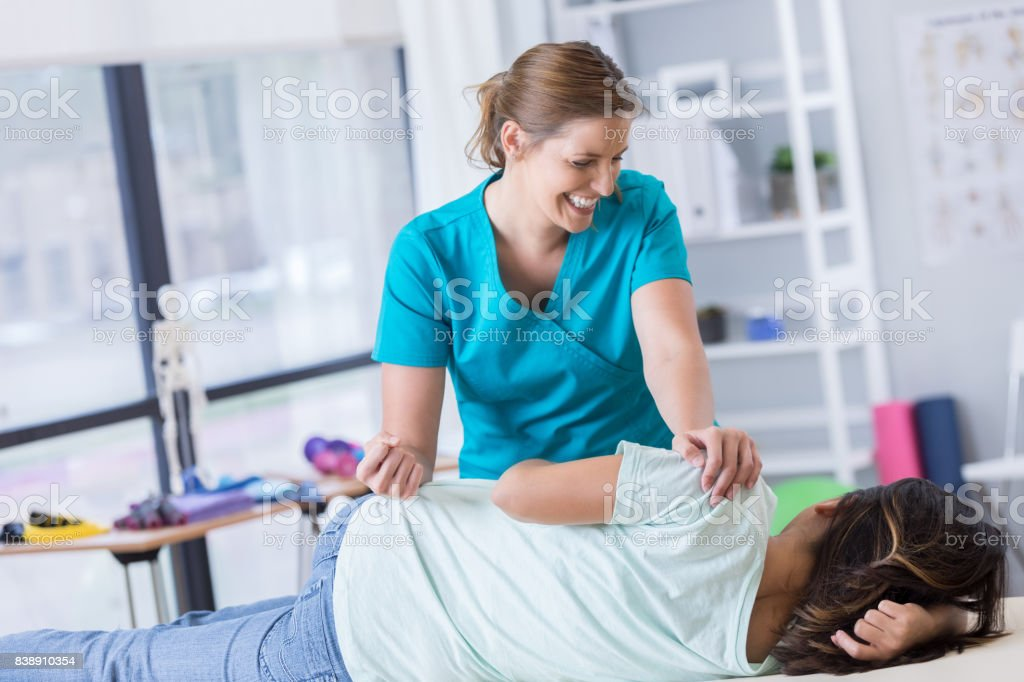 Chiropractor adjusts female patient
