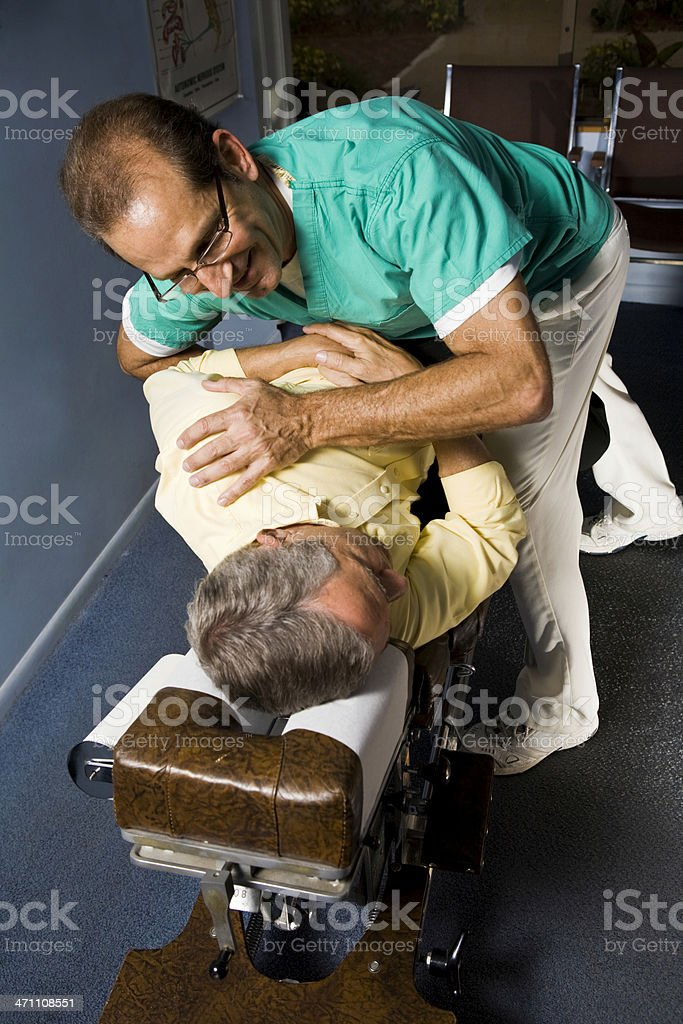Chiropractor making adjusting to senior patient royalty-free stock photo