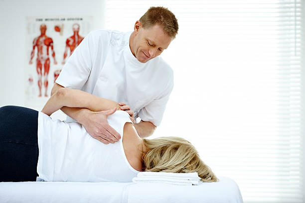 chiropractor massaging back of female patient - osteopathy stock pictures, royalty-free photos & images