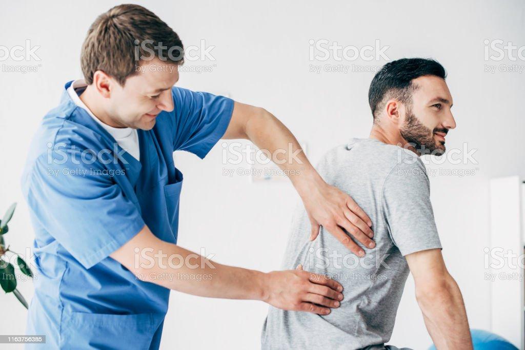 Chiropraktiker massiert zurück von gut aussehenden Mann im Krankenhaus - Lizenzfrei Arzt Stock-Foto
