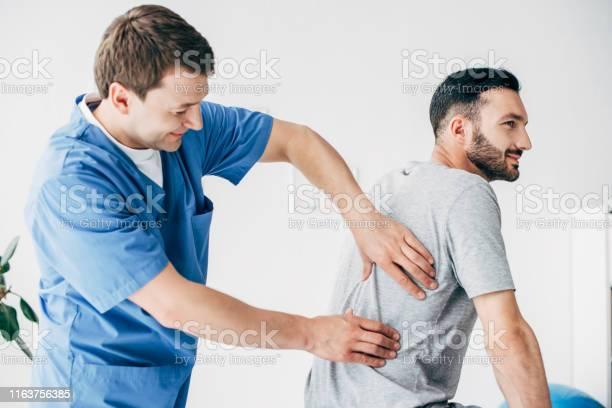 Chiropraktiker Massiert Zurück Von Gut Aussehenden Mann Im Krankenhaus Stockfoto und mehr Bilder von Arzt