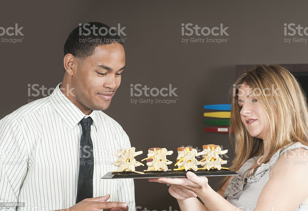 Chiropractor Showing Spine Model to Patient royalty-free stock photo