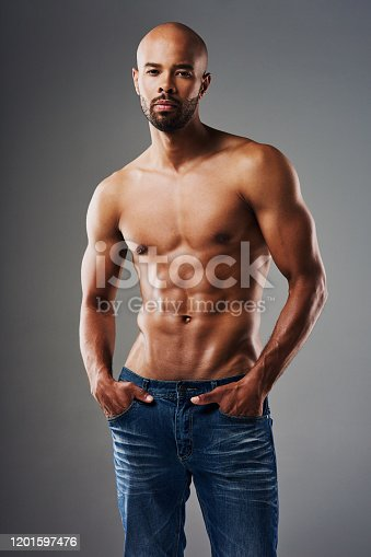 Portrait of a handsome young man posing shirtless against a grey background
