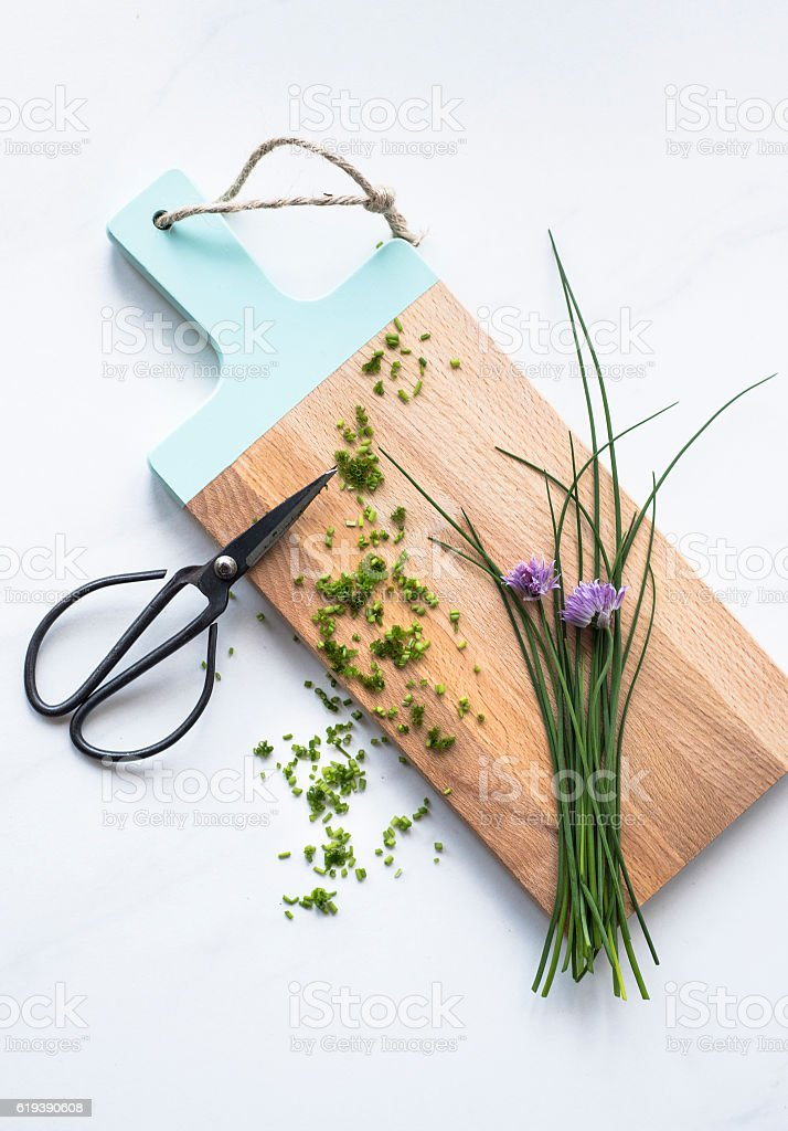 Chive on cutting board with scissors stock photo