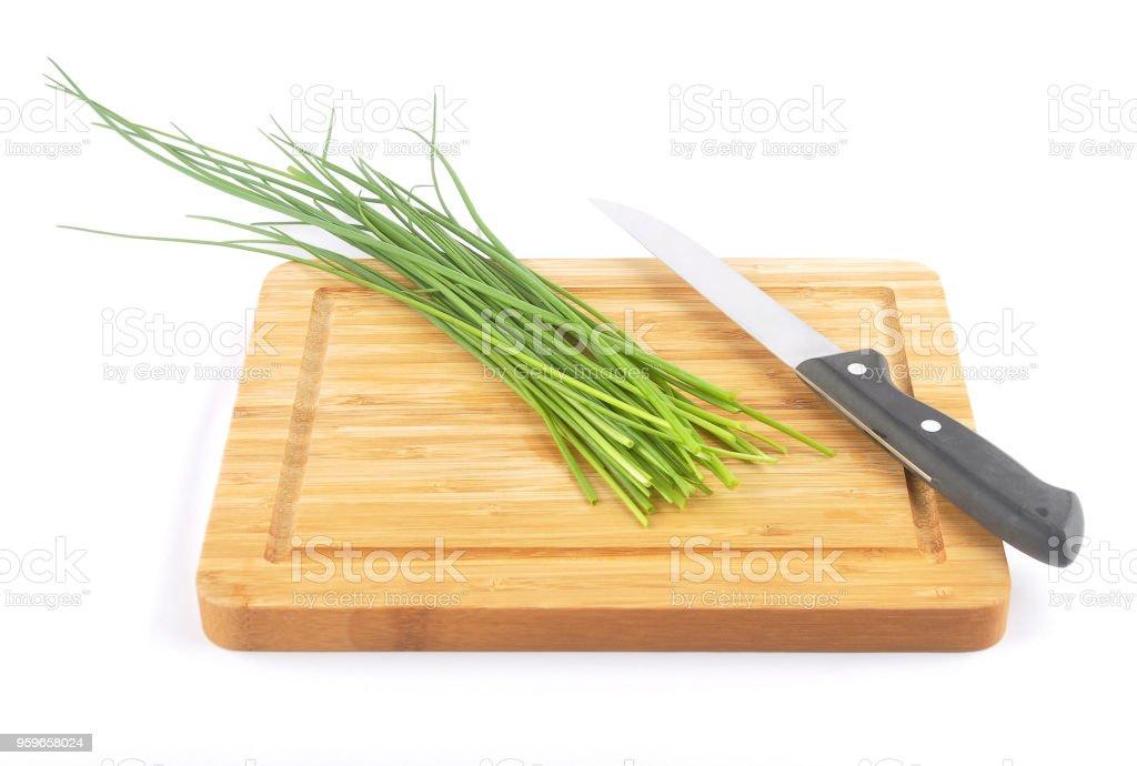 Cebolletas con cuchillo de mesa y tablero de corte en blanco - Foto de stock de Aderezo libre de derechos