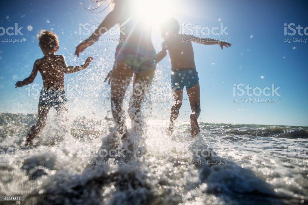 Chlidren running happily in the sea stock photo