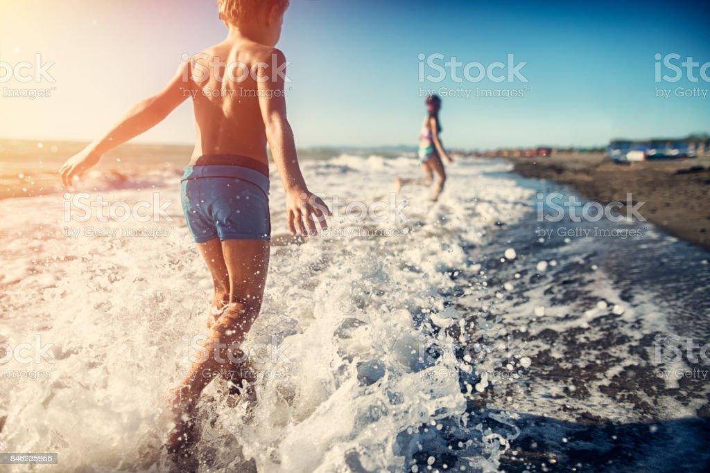 Chlidren running on the beach stock photo