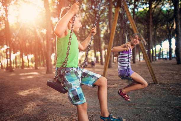 Chlidren swinging in pine forest playground stock photo