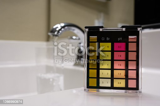 Picture of a Chlorine and PH water testing kit showing that the water has high chlorine and is probably not safe to drink. In the background you can see a faucet and water being poured into a glass. This tells you that the tap water is what has the high chlorine content.
