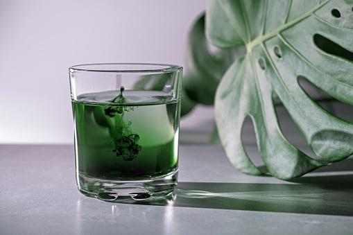 Chlorophyll extract is poured in pure water in glass against a white grey background with green leaf. Liquid chlorophyll in a glass of water. Concept of superfood, healthy eating, detox and diet. Slow motion, close up, copy space