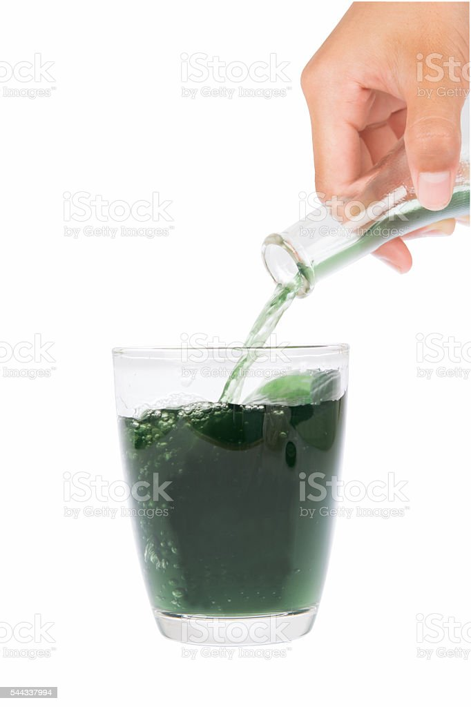 chlorophyll Flows in to the bottle by hand glass stock photo