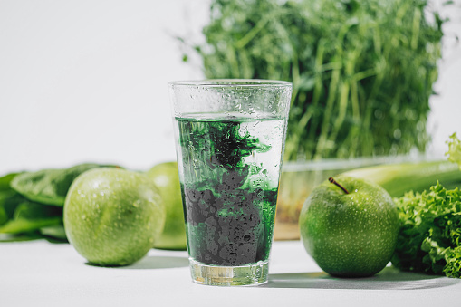chlorophyll in a glass of water on a white background near are various fresh vegetables fruits and roots with lettuce and spinach