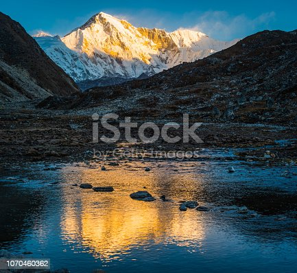 Golden light of sunrise illuminating the snow capped summit of Cho Oyu, the 8188m Himalayan mountain peak on the Nepal Tibet border, reflecting in the clear waters of Gokyo, deep in the Sagarmatha National Park.