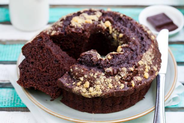chocolat-gugelhupf. bunten hölzernen hintergrund. - schokoladen biskuitkuchen stock-fotos und bilder