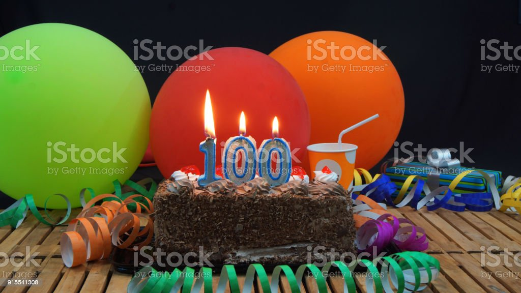 Chocolate 100 Birthday Cake With Candles Burning On Rustic Wooden Table Background Of Colorful Balloons