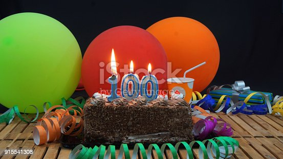 Chocolate 100 Birthday Cake With Candles Burning On Rustic Wooden Table Background Of Colorful Balloons Gifts Plastic Cups And Streamers Black