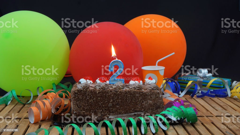 Chocolate 2 Birthday Cake With Candles Burning On Rustic Wooden Table Background Of Colorful Balloons Gifts Plastic Cups And Streamers Black