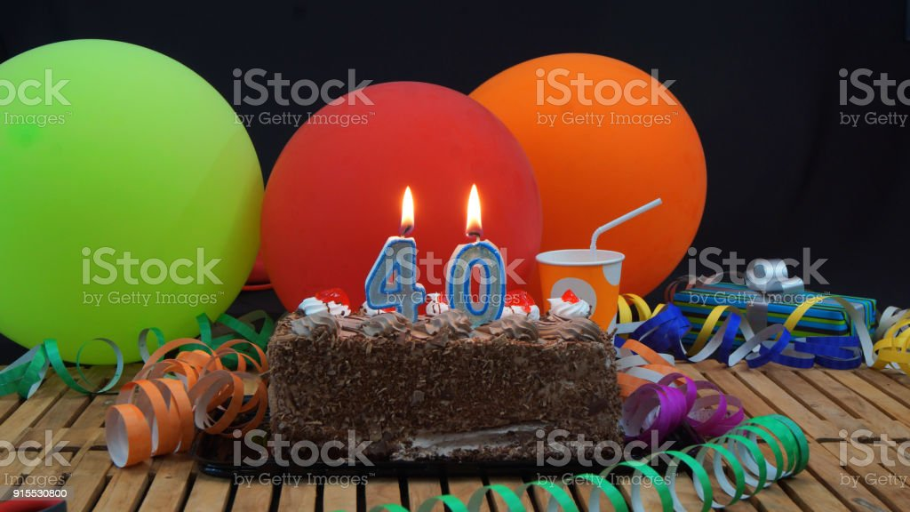 Chocolate 40 Birthday Cake With Candles Burning On Rustic Wooden Table Background Of Colorful Balloons Gifts Plastic Cups And Streamers Black