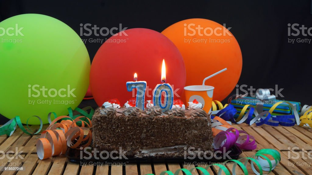 Chocolate 70 Birthday Cake With Candles Burning On Rustic Wooden Table Background Of Colorful Balloons