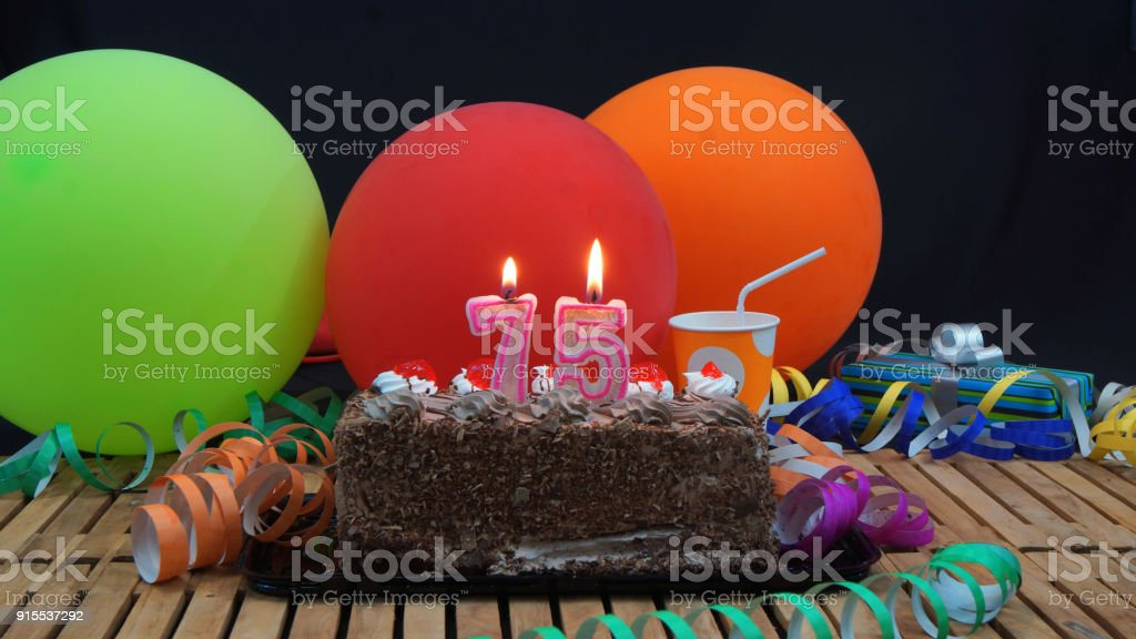 Chocolate 75 Birthday Cake With Candles Burning On Rustic Wooden Table Background Of Colorful Balloons Gifts Plastic Cups And Streamers Black