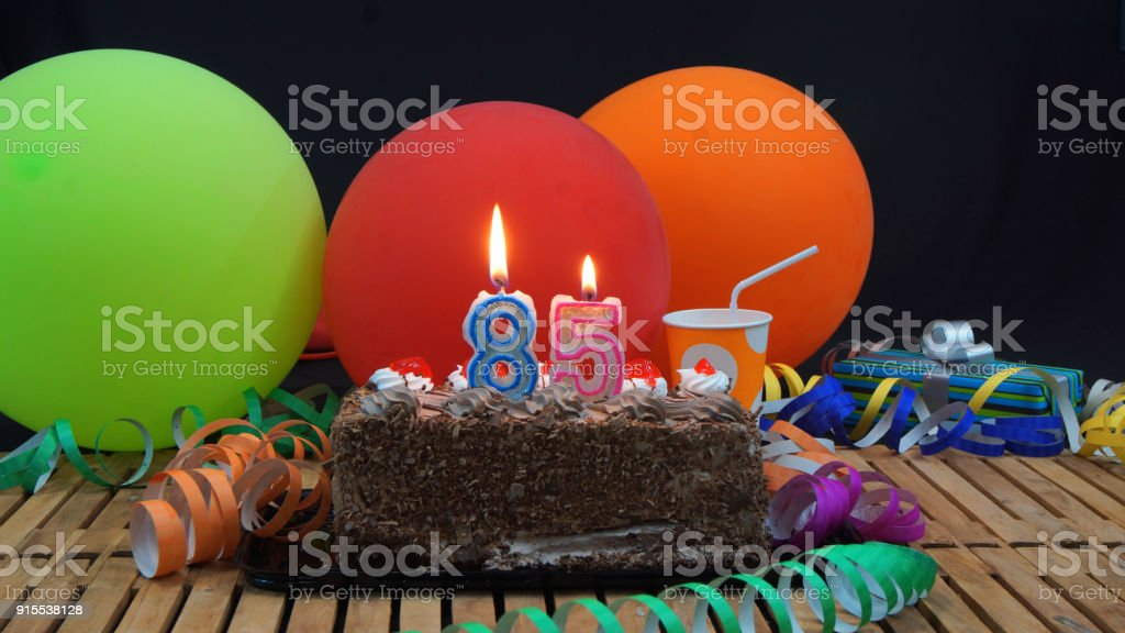 Chocolate 85 Birthday Cake With Candles Burning On Rustic Wooden