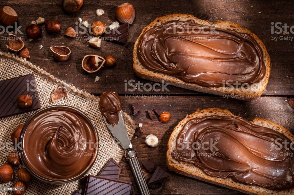 Chocolate and hazelnut spread on bread slices shot on rustic wooden table stock photo