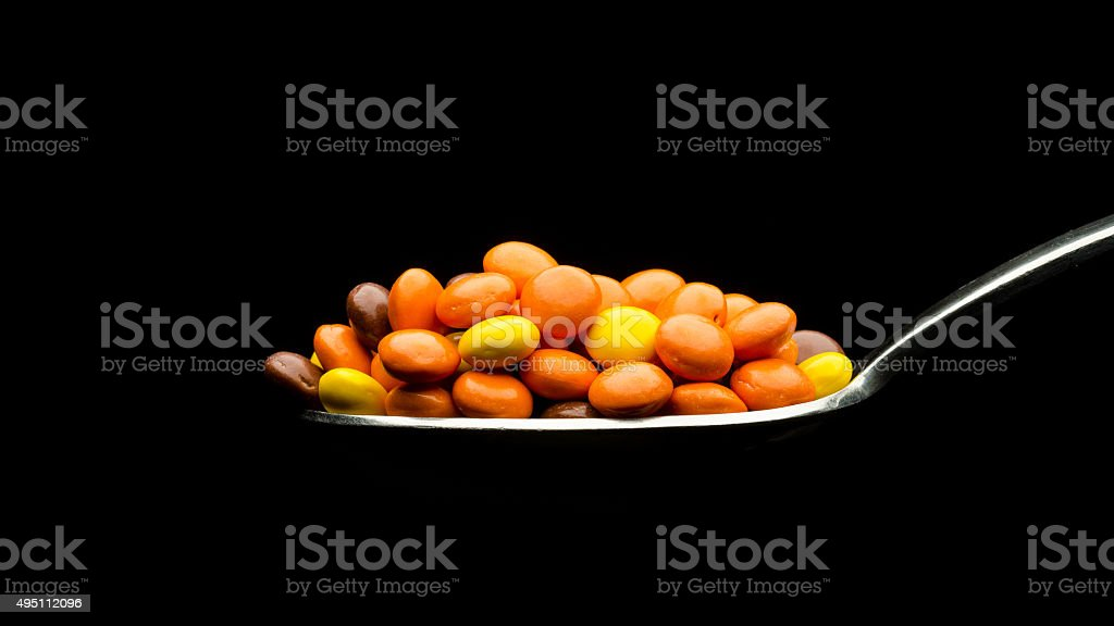 Chocolate and peanut butter candies on a spoon stock photo