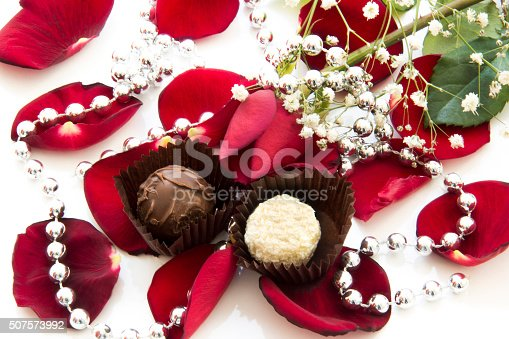 istock Chocolate and red rose among the rose petals 507573992