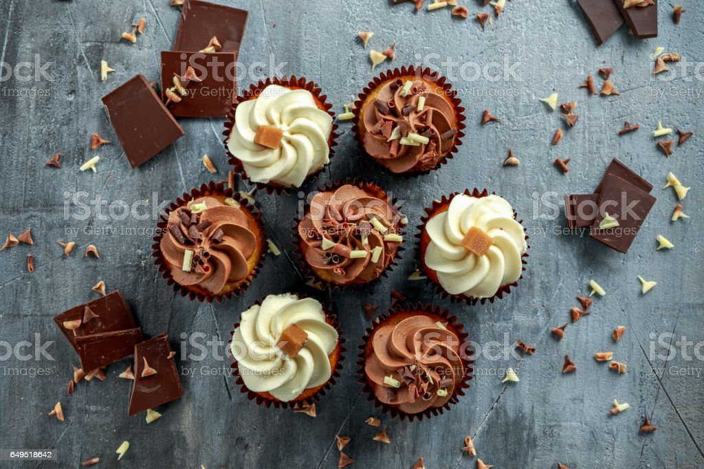 Chocolate and vanilla caramel cupcakes served with dark and white chocolate chippings stock photo