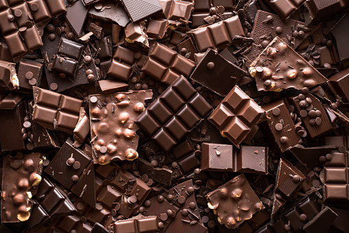 Assorted chocolate bar and chunks, background. Flat lay with a multitude of chocolate kinds. Delicious cocoa dessert. Baking chocolate collection.