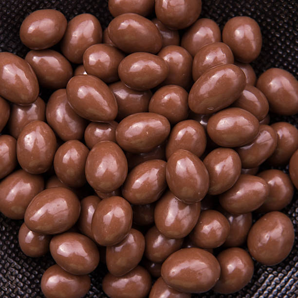 Chocolate ball candy on black background with nuts inside stock photo