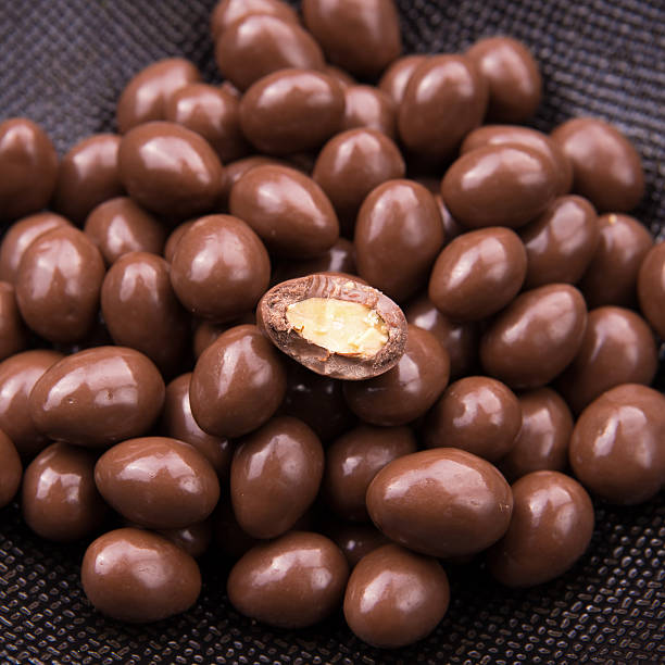 Chocolate ball candy smarties on black background with nuts inside stock photo
