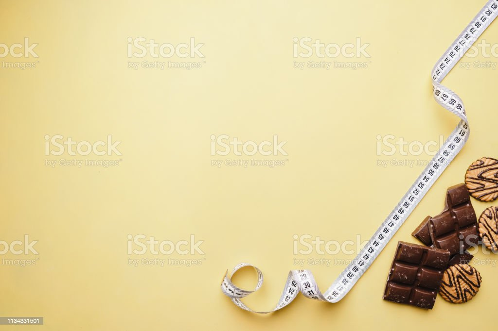 chocolate bar and measure tape. diet and fitness stock photo