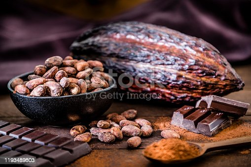 Front view of some dark chocolate bars, cocoa powder, cocoa seeds and cocoa pods on a dark brown wooden plank. Selective focus on the cocoa beans. Low key DSLR photo taken with Canon EOS 6D Mark II and Canon EF 24-105 mm f/4L