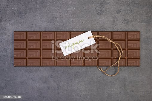 sweet bar of chocolate lies on a gray stone background with a label that says vegan and a vintage string