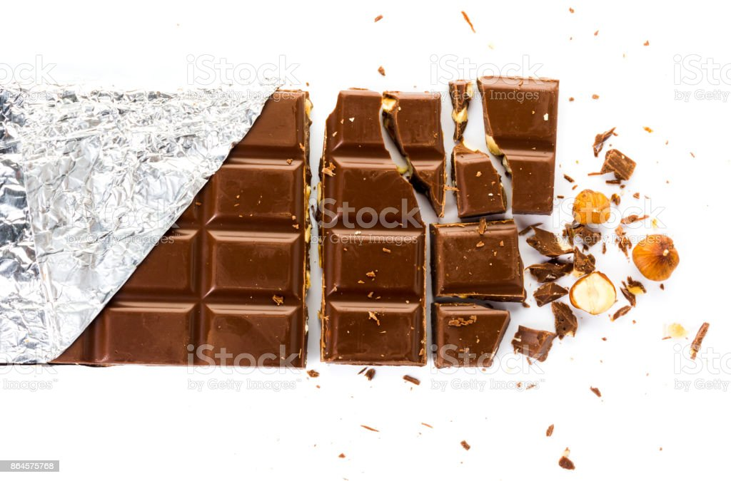 chocolate bar with hazelnuts broken into pieces on a white background stock photo