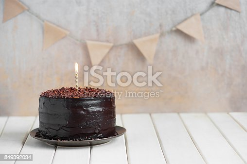 istock Chocolate birthday cake with burning candle 849392034