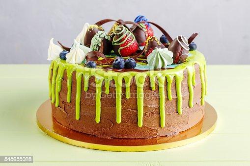 istock Chocolate birthday cake with fruit and green glaze 545655028