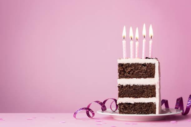 chocolate birthday cake with pink candles - кусок торта стоковые фото и изображения