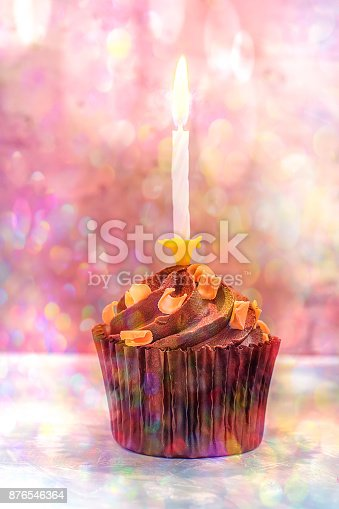1058078946 istock photo Chocolate Birthday Cupcake with Buttercream Caramel Swirl Sprinkles. Single Lit Burning Candle. Colorful Confetti Lights Flare Pastel Colors. Festive Magic Greeting Card Copy Space. Toned 876546364